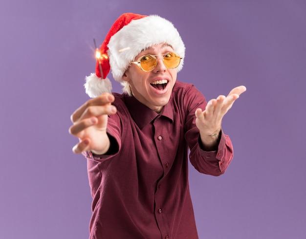 Pod wrażeniem młody blondyn w czapce mikołaja i okularach wyciągając świąteczny brylant pokazujący pustą dłoń na fioletowej ścianie