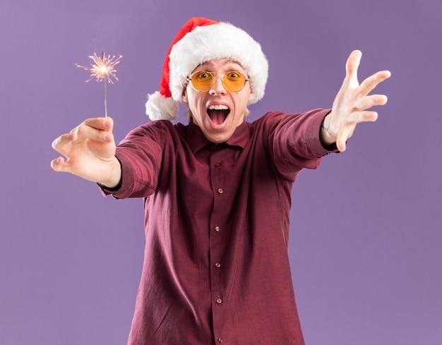 Pod wrażeniem młody blondyn w kapeluszu mikołaja i okularach wyciągając świąteczny brylant i ręka robi gest powitalny na fioletowej ścianie
