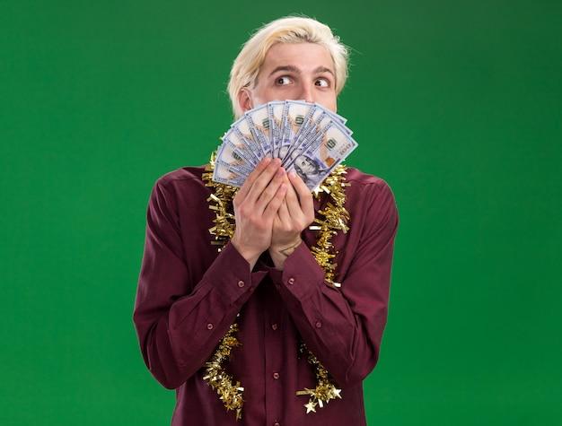 Pod wrażeniem młody blondyn w okularach z świecącą girlandą na szyi trzymający pieniądze patrząc z boku z tyłu odizolowany na zielonej ścianie z miejscem na kopię
