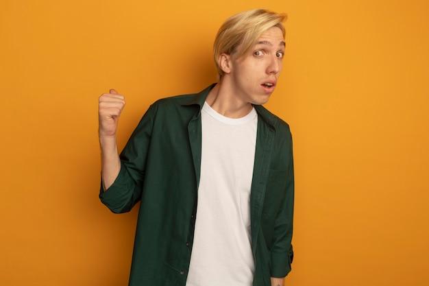 Pod wrażeniem młody blondyn w zielonej koszulce wskazuje na tył
