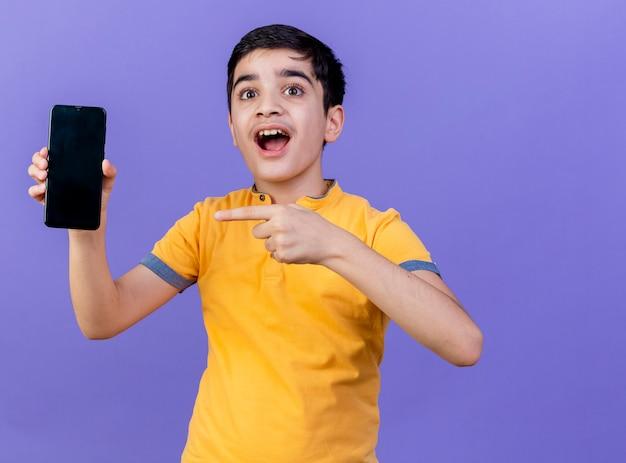 Pod wrażeniem młody chłopak pokazuje i wskazuje na telefon komórkowy patrząc z przodu na białym tle na fioletowej ścianie