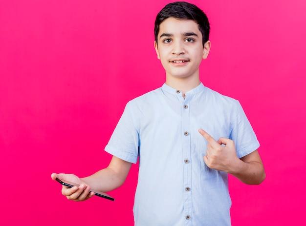 Pod wrażeniem młody chłopak trzymając telefon komórkowy patrząc na przód, wskazując na bok na białym tle na różowej ścianie