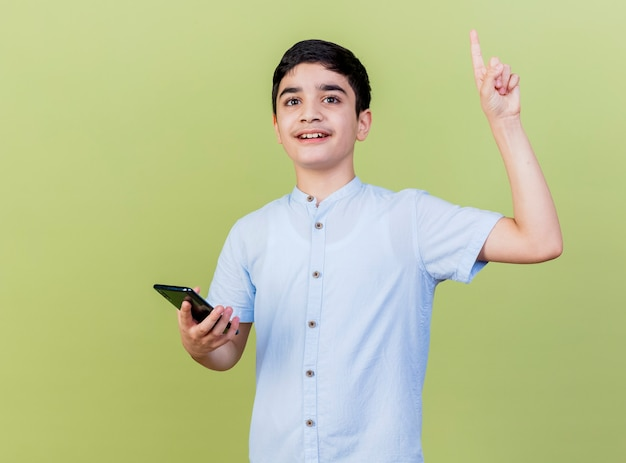 Pod wrażeniem młody chłopak trzymając telefon komórkowy patrząc z przodu skierowaną w górę na białym tle na oliwkowej ścianie