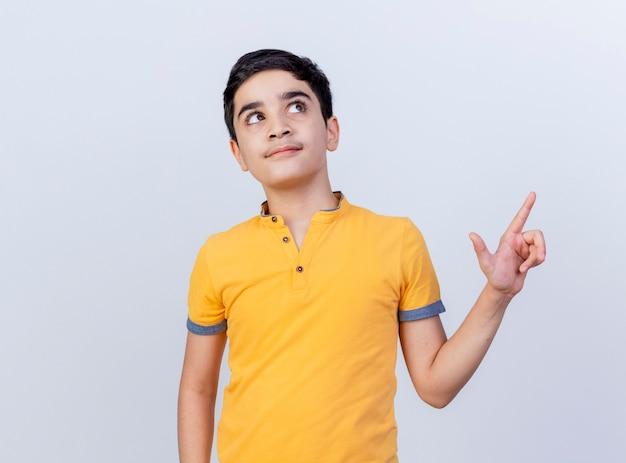 Pod wrażeniem młody chłopiec kaukaski patrząc i wskazując na bok na białym tle na białym tle z miejsca na kopię