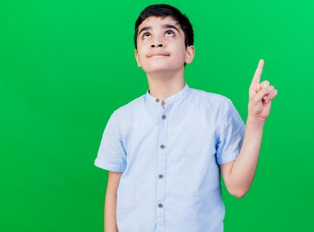 Pod wrażeniem młody chłopiec kaukaski patrząc i wskazując w górę na białym tle na zielonej ścianie z miejsca na kopię
