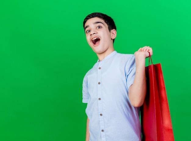 Pod wrażeniem młody chłopiec kaukaski trzymając torbę na zakupy na białym tle na zielonej ścianie z miejsca na kopię