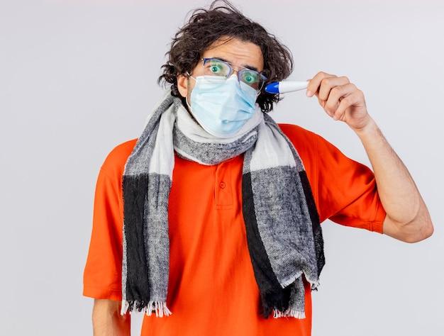 Pod wrażeniem młody chory człowiek w okularach i masce trzymając termometr patrząc z przodu na białym tle na białej ścianie