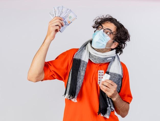 Pod wrażeniem młody chory człowiek w okularach szalik i maska trzyma pieniądze i pigułki patrząc na pieniądze na białej ścianie