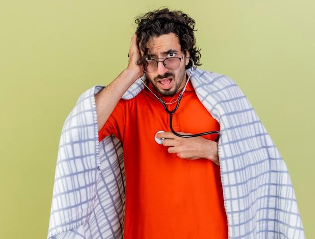 Pod wrażeniem młody chory mężczyzna w okularach i stetoskop owinięty w kratę słuchający bicia własnego serca, patrząc z przodu, kładąc dłoń na głowie odizolowaną na oliwkowej ścianie