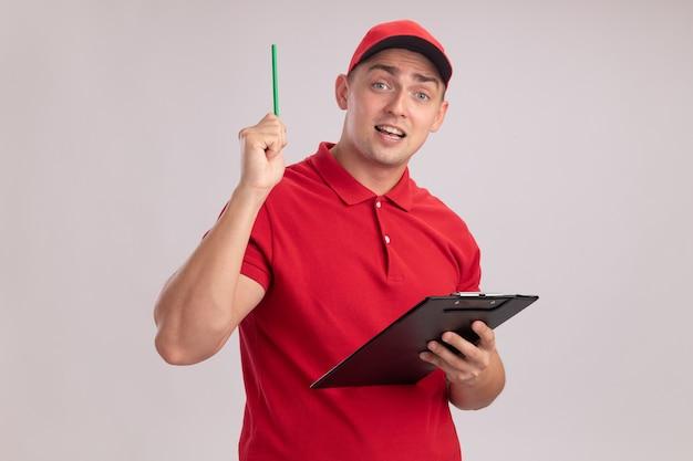 Pod wrażeniem młody człowiek dostawy ubrany w mundur z czapką trzymając schowek podnoszący ołówek na białej ścianie