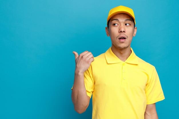 Pod wrażeniem młody człowiek dostawy w mundurze i czapce, patrząc i wskazując na bok