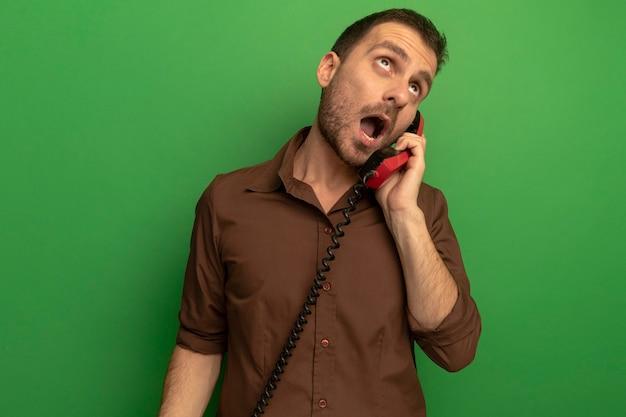 Pod wrażeniem młody człowiek kaukaski patrząc w górę rozmawia przez telefon na białym tle na zielonej ścianie z miejsca na kopię