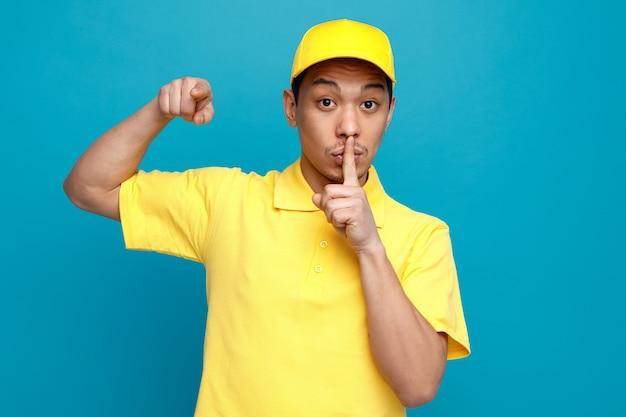 Pod wrażeniem młody dostawca ubrany w mundur i czapkę, wskazując na bok, wykonując gest ciszy