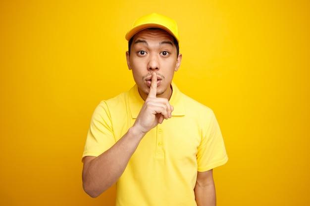 Pod wrażeniem młody dostawca w czapce i mundurze robi gest ciszy