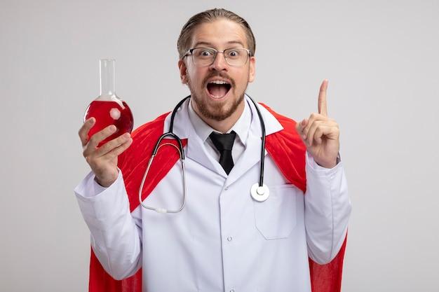 Pod wrażeniem młody facet superbohatera w szacie medycznej ze stetoskopem i okularami trzymającymi szklaną butelkę chemii wypełnioną czerwonym płynem i wskazuje na górę na białym tle