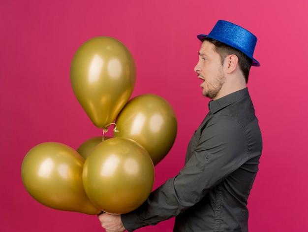 Pod wrażeniem młody imprezowicz na sobie niebieski kapelusz, trzymając i patrząc na balony na różowym tle