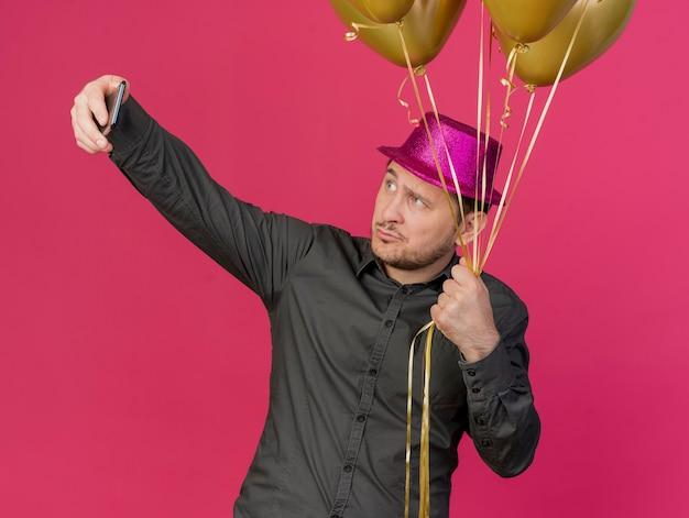 Pod wrażeniem młody imprezowicz w różowym kapeluszu trzymając balony i zrób selfie na różowo