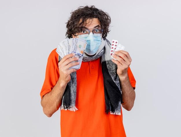 Pod wrażeniem młody kaukaski chory mężczyzna w okularach szalik i maska, trzymając pieniądze i pigułki medyczne, patrząc na kamerę na białym tle z miejsca na kopię