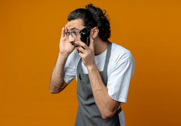 Pod wrażeniem młody kaukaski fryzjer męski w mundurze i okularach trzymający maszynkę do strzyżenia włosów dotykający głowy i patrząc w bok na białym tle na pomarańczowym tle z miejscem na kopię