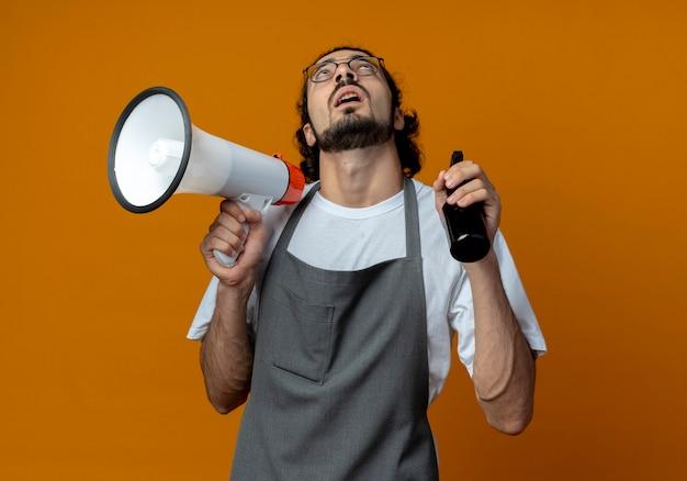 Pod wrażeniem młody kaukaski fryzjer męski w okularach i falującej opasce do włosów w mundurze, patrząc w górę, trzymając butelkę z rozpylaczem i głośnik odizolowany na pomarańczowym tle
