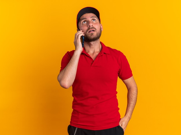 Pod wrażeniem młody kaukaski mężczyzna dostawy w czerwonym mundurze i czapce, trzymając rękę w kieszeni, rozmawiając przez telefon, patrząc w górę na pomarańczowej ścianie z miejscem na kopię