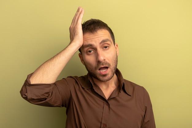 Pod wrażeniem młody kaukaski mężczyzna patrząc na aparat robi aww teraz pamiętam, o czym zapomniałem gestu na tle oliwkowej zieleni