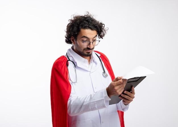 Pod wrażeniem młody kaukaski mężczyzna superbohatera w okularach optycznych w mundurze lekarza z czerwonym płaszczem i stetoskopem na szyi trzyma i patrzy na schowek