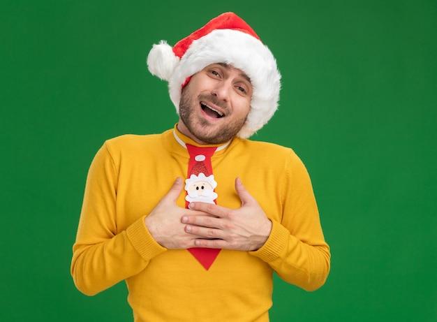 Pod wrażeniem młody kaukaski mężczyzna ubrany w świąteczny kapelusz i krawat, patrząc na kamery, robi dziękuję gest na białym tle na zielonym tle