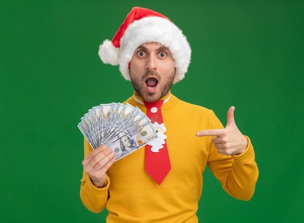 Pod wrażeniem młody kaukaski mężczyzna ubrany w świąteczny kapelusz i krawat, trzymając i wskazując na pieniądze na białym tle na zielonym tle
