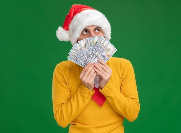 Pod wrażeniem młody kaukaski mężczyzna ubrany w świąteczny kapelusz i krawat, trzymając pieniądze patrząc od tyłu na białym tle na zielonym tle