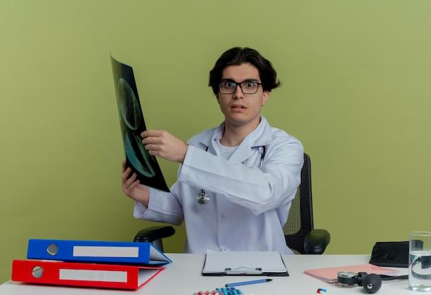 Pod wrażeniem młody lekarz płci męskiej ubrany w szlafrok medyczny i stetoskop w okularach siedzi przy biurku z narzędziami medycznymi trzymającymi zdjęcie rentgenowskie patrząc na białym tle