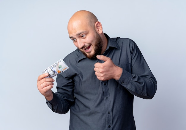 Pod wrażeniem młody łysy mężczyzna call center gospodarstwa i patrząc na pieniądze, trzymając rękę na powietrzu na białym tle