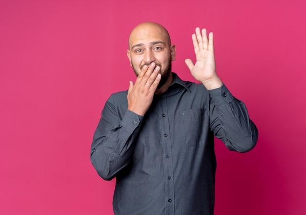 Pod wrażeniem młody łysy mężczyzna call center podnosząc rękę i kładąc inny na ustach na białym tle na karmazynowy z miejsca na kopię