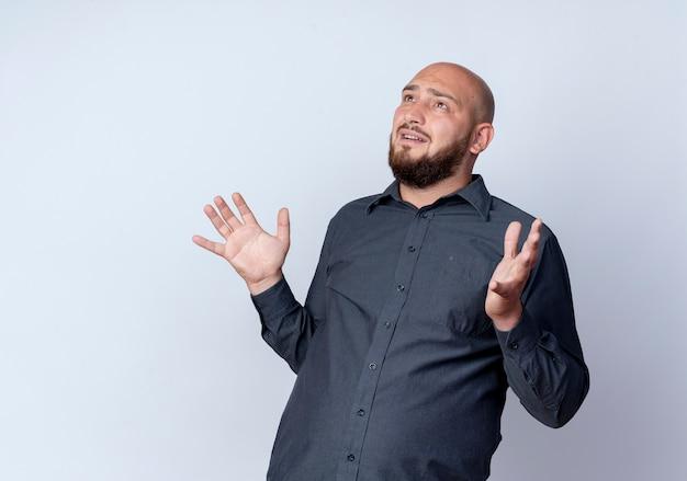 Pod wrażeniem młody łysy mężczyzna call center pokazując puste ręce patrząc w górę na białym tle na biały z miejsca na kopię