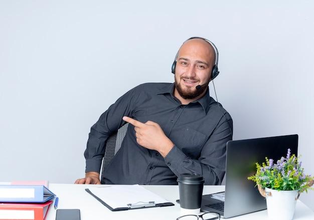 Pod wrażeniem młody łysy mężczyzna call center sobie zestaw słuchawkowy siedzi przy biurku z narzędzi pracy, wskazując na bok na białym tle