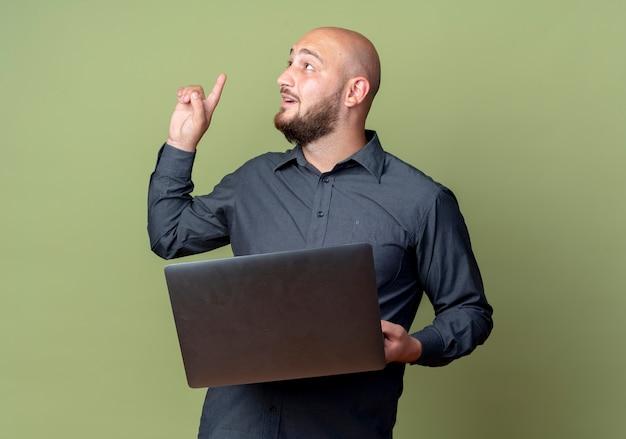 Pod wrażeniem młody łysy mężczyzna call center trzyma laptopa patrząc i skierowaną w górę na białym tle na oliwkowej zieleni z miejsca na kopię