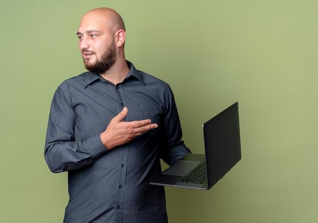 Pod wrażeniem młody łysy mężczyzna call center trzymając i wskazując ręką na laptopie i patrząc na bok na białym tle na oliwkowej zieleni z miejsca na kopię