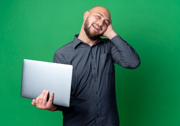 Pod wrażeniem młody łysy mężczyzna call center trzymając laptop i kładąc rękę na głowie na białym tle na zielono z miejsca na kopię