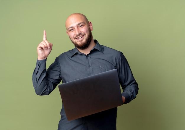 Pod wrażeniem młody łysy mężczyzna call center trzymając laptop i podnosząc palec na białym tle oliwkowej zieleni z miejsca na kopię