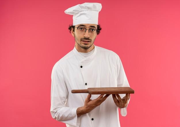 Pod wrażeniem młody mężczyzna kucharz w mundurze szefa kuchni i okularach trzyma deskę do krojenia