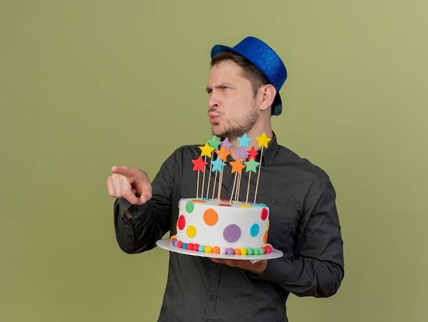 Pod wrażeniem młody partyjny facet ubrany w czarną koszulę i niebieski kapelusz, trzymając ciasto i wskazuje na bok na białym tle na oliwkowej zieleni