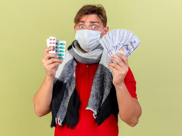 Pod wrażeniem młody przystojny blondyn chory ubrany w maskę, trzymając pieniądze i paczki pigułek medycznych na oliwkowej ścianie