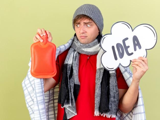 Pod wrażeniem młody przystojny blondyn chory w czapce zimowej i szaliku owiniętym w kratę, trzymając bańkę pomysłu i butelkę z gorącą wodą, patrząc na butelkę z gorącą wodą na tle oliwkowej zieleni