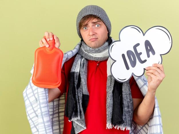 Pod wrażeniem młody przystojny blondyn chory w czapce zimowej i szaliku owiniętym w kratę, trzymając bańkę pomysłu i butelkę z gorącą wodą, patrząc na kamerę odizolowaną na oliwkowym tle
