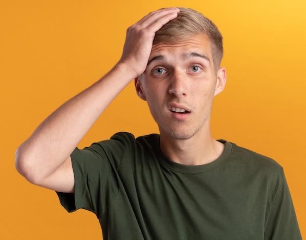 Pod wrażeniem młody przystojny facet na sobie zieloną koszulę kładąc rękę na głowie na białym tle na żółtej ścianie