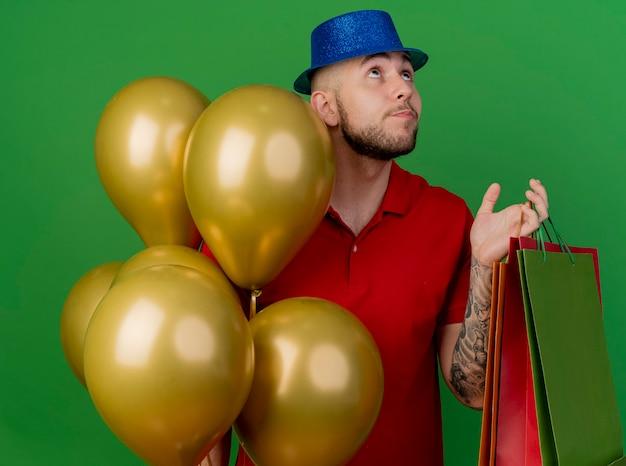 Pod wrażeniem młody przystojny facet słowiańskich partii na sobie kapelusz imprezowy stojący w pobliżu balonów, trzymając papierowe torby patrząc w górę na białym tle na zielonym tle