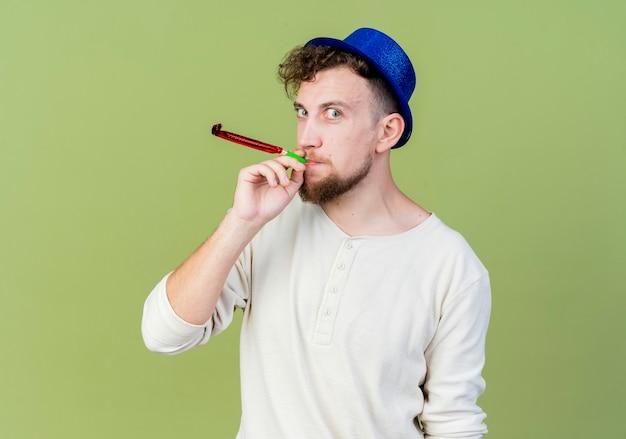 Pod wrażeniem młody przystojny facet słowiańskich partii na sobie kapelusz partii patrząc na kamery dmuchanie dmuchawy party na białym tle na oliwkowym tle
