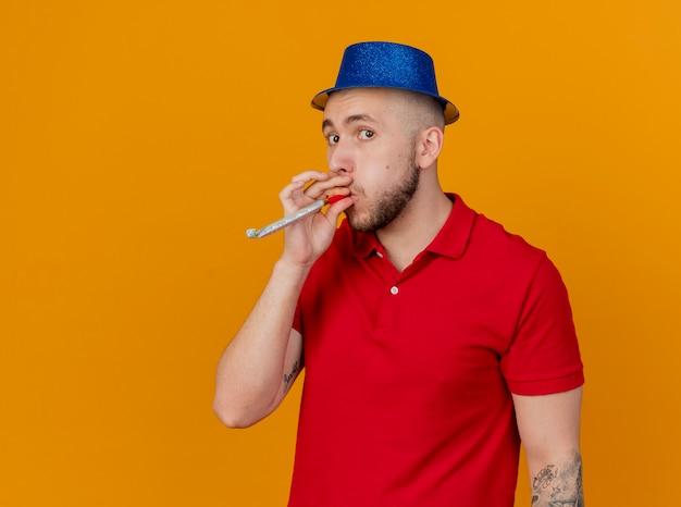 Pod wrażeniem młody przystojny facet słowiańskich partii na sobie kapelusz partii patrząc na kamery dmuchanie dmuchawy party na białym tle na pomarańczowym tle z miejsca na kopię