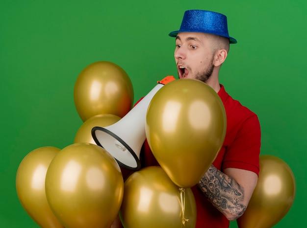 Pod wrażeniem młody przystojny facet słowiańskich partii na sobie kapelusz partii stojącej wśród balonów patrząc w dół, rozmawiając przez głośnik na białym tle na zielonym tle