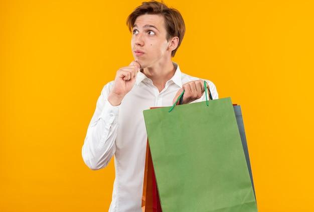 Pod wrażeniem młody przystojny facet ubrany w białą koszulę trzymający torby chwycił podbródek